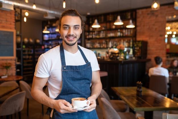 Jovem garçom alegre de camiseta branca e avental azul segurando uma xícara de cappuccino no pires enquanto olha para você