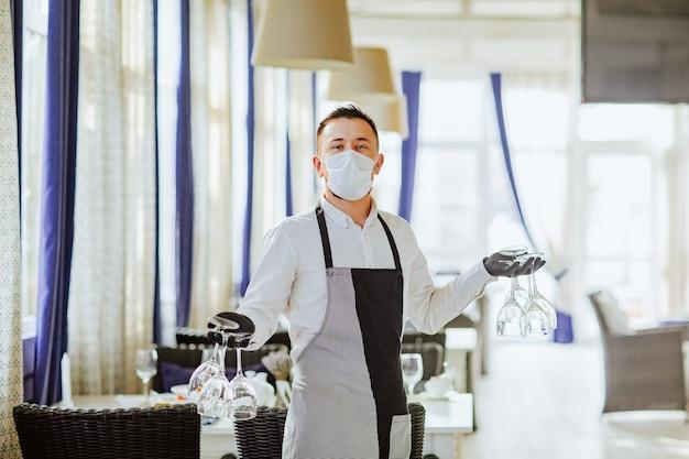 Jovem garçom com máscara médica, luvas e avental posando com um monte de taças de vinho no restaurante.