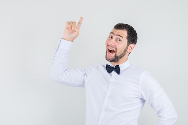 Jovem garçom de camisa branca, apontando o dedo para cima e parecendo feliz, vista frontal.