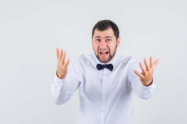 Jovem garçom de camisa branca gritando com as mãos de maneira agressiva e parecendo agitado, vista frontal.