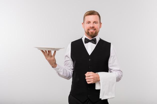 Jovem garçom elegante com colete preto e gravata borboleta segurando uma toalha branca e um prato enquanto fica em pé na frente da câmera, isolado