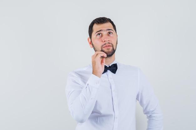 Jovem garçom em camisa branca, olhando para cima com os dedos no queixo e olhando pensativo, vista frontal.