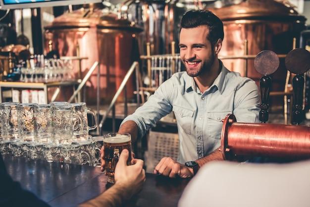 Jovem garçom está dando cerveja para clientes e sorrindo.