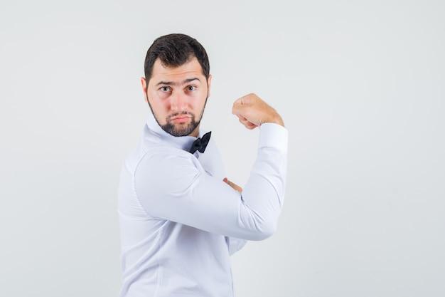 Jovem garçom mostrando os músculos do braço em camisa branca e parecendo poderoso. .