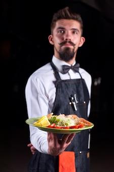 Jovem garçom oferece aos visitantes um prato apetitoso em um evento festivo.