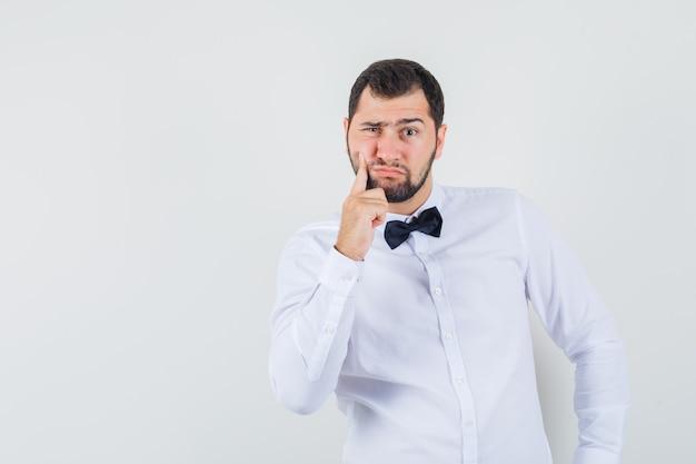 Jovem garçom sofrendo de dor de dente na camisa branca e parecendo preocupado, vista frontal.