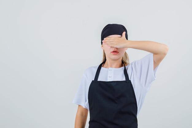 Jovem garçonete cobrindo os olhos com a mão de uniforme e avental