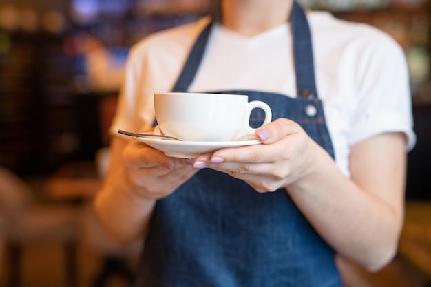 Jovem garçonete com avental azul segurando ou carregando uma xícara de chá ou cappuccino no pires para um dos clientes de um café ou restaurante