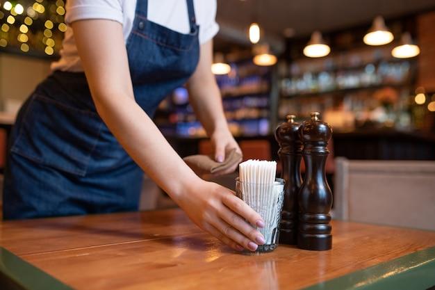 Jovem garçonete de avental colocando copo com palitos de dente na mesa de madeira enquanto prepara o lugar para novos hóspedes em um café ou restaurante