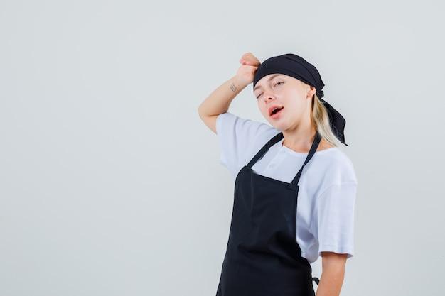 Jovem garçonete de uniforme e avental apoiando a cabeça na mão e piscando os olhos