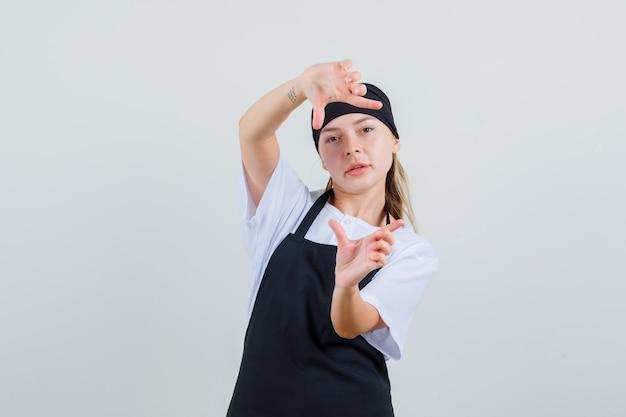 Jovem garçonete de uniforme e avental fazendo gesto de moldura