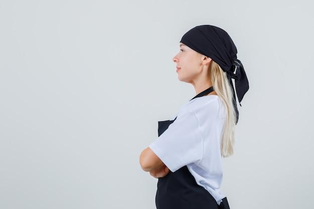 Jovem garçonete em pé com os braços cruzados de uniforme e avental e olhando focado.