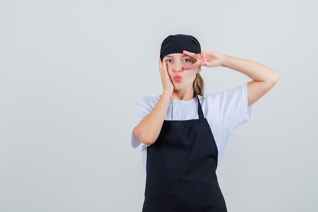 Jovem garçonete mostrando o sinal-v com lábios dobrados, uniforme e avental