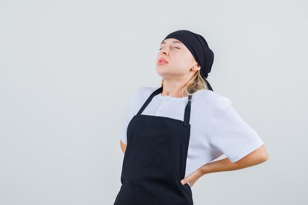 Jovem garçonete sofrendo de dores nas costas de uniforme e avental e parecendo cansada