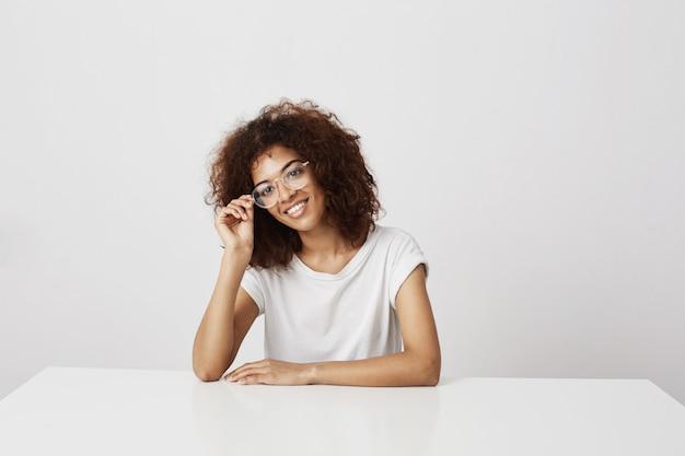 Jovem garota africana atraente em copos sorrindo sentado à mesa sobre parede branca