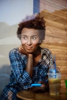 Jovem garota africana bonita sorrindo, segurando o telefone, sentado no café. atirado de fora.
