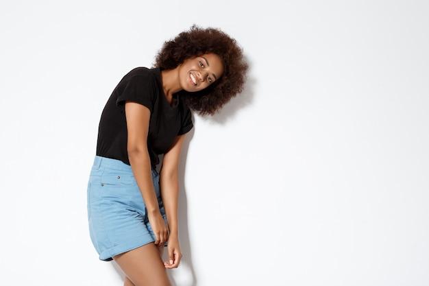 Jovem garota africana bonita sorrindo sobre parede branca
