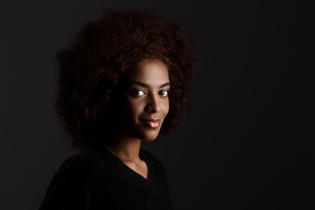 Jovem garota africana bonita sorrindo sobre parede escura