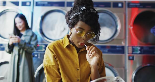 Jovem garota afro-americana bonita de óculos amarelos, sentado na sala de serviço de lavanderia. mulher com pirulito lendo revista enquanto aguarda a roupa ser lavada. clientes do sexo feminino.