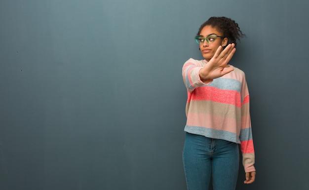 Jovem garota afro-americana com olhos azuis, colocando a mão na frente