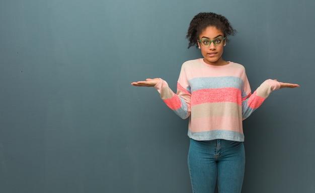 Jovem garota afro-americana com olhos azuis confusos e duvidosos