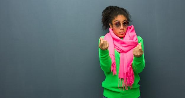 Jovem garota afro-americana, com olhos azuis, fazendo um gesto de necessidade