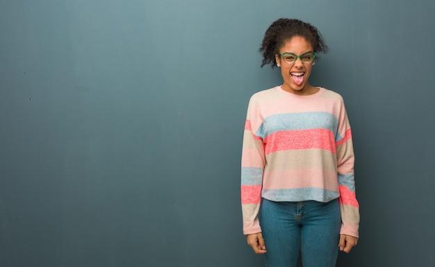Jovem garota afro-americana com olhos azuis funnny e língua mostrando amigável