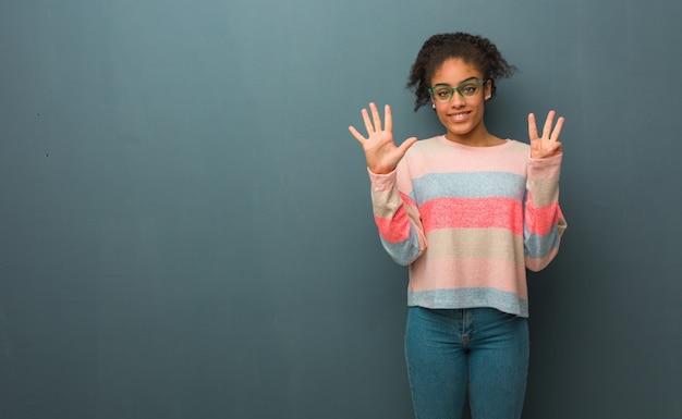 Jovem garota afro-americana com olhos azuis, mostrando o número oito