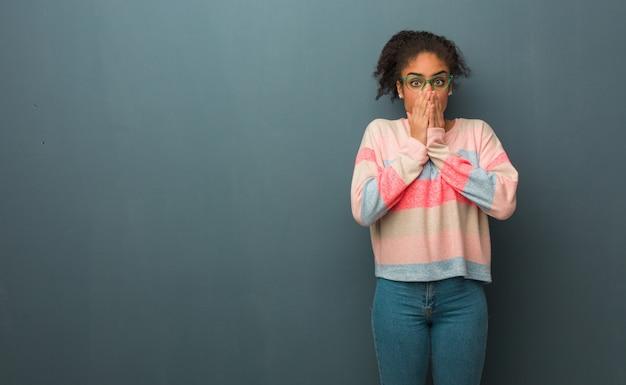 Jovem garota afro-americana com olhos azuis muito assustada e com medo escondido