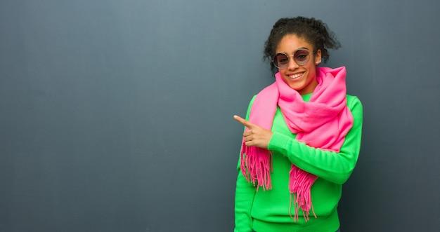 Jovem garota afro-americana com olhos azuis, sorrindo e apontando para o lado