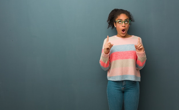 Jovem garota afro-americana com olhos azuis surpreso apontando para cima para mostrar algo