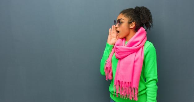Jovem garota afro-americana com olhos azuis sussurrando um tom de fofoca