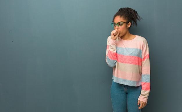 Jovem garota afro-americana com olhos azuis, tossindo, doente devido a um vírus