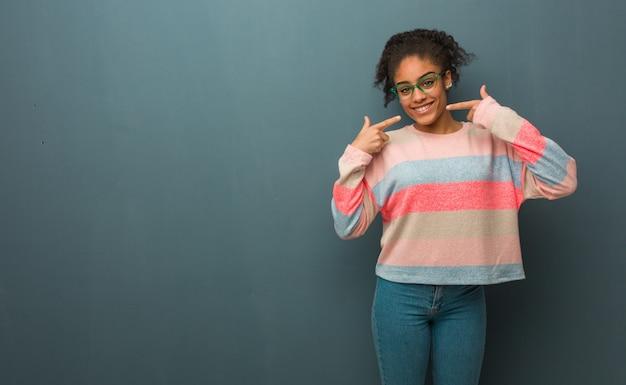 Jovem garota afro-americana com sorrisos de olhos azuis, apontando a boca