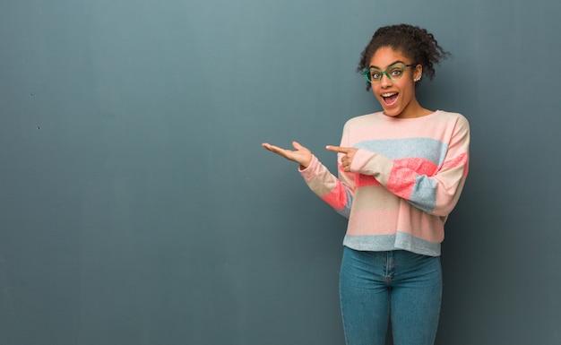 Jovem garota afro-americana de olhos azuis, segurando algo com a mão