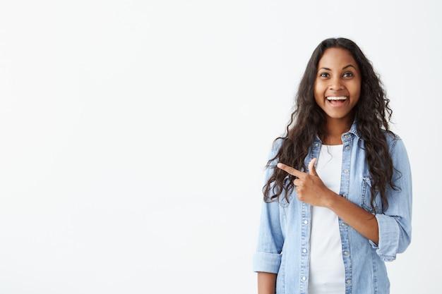 Jovem garota afro-americana espantada com longos cabelos ondulados, olhando com a boca aberta, mostrando os dentes, apontando o dedo para uma parede branca com espaço de cópia para o seu anúncio ou promoção
