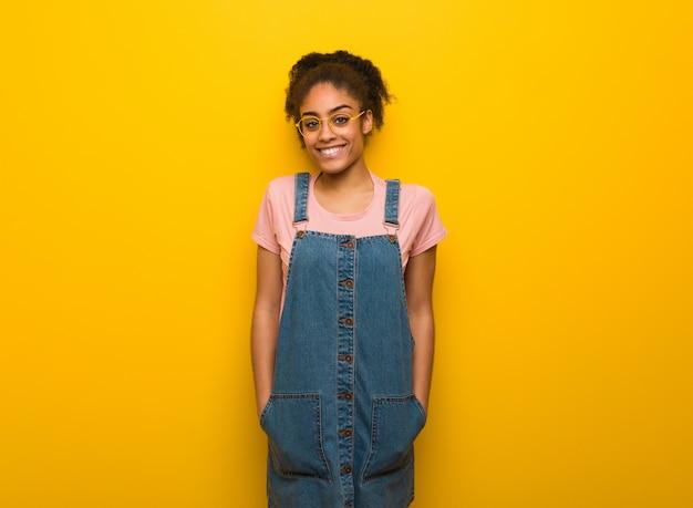 Jovem garota afro-americana negra com olhos azuis, alegre com um grande sorriso