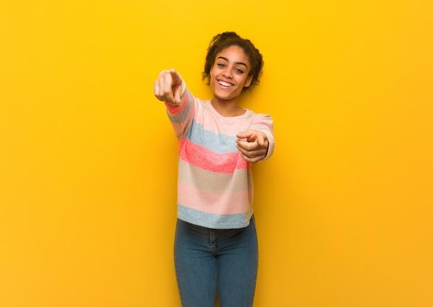 Jovem garota afro-americana negra com olhos azuis, alegre e sorridente