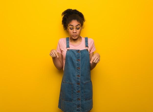 Jovem garota afro-americana negra com olhos azuis, apontando para baixo