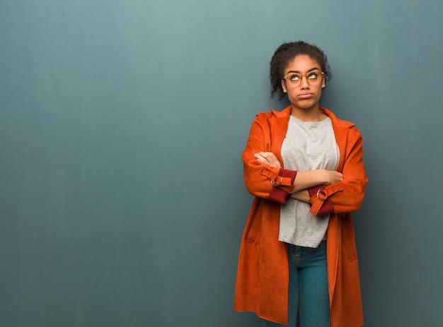 Jovem garota afro-americana negra com olhos azuis, cansada e entediada