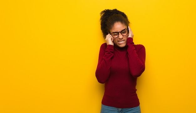 Jovem garota afro-americana negra com olhos azuis, cobrindo os ouvidos com as mãos