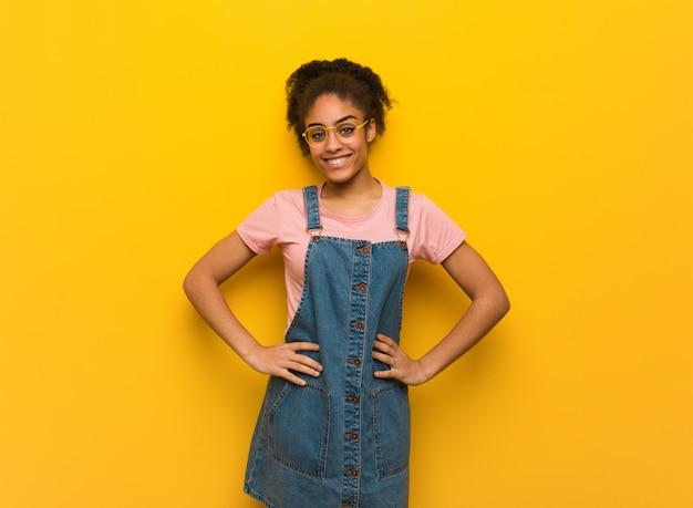 Jovem garota afro-americana negra com olhos azuis, com as mãos nos quadris