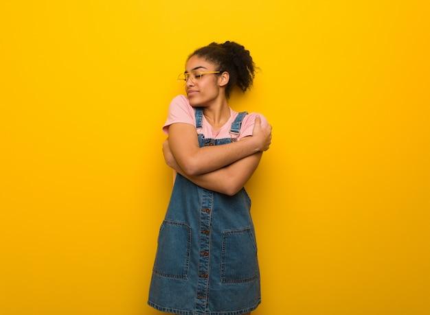 Jovem garota afro-americana negra com olhos azuis, dando um abraço