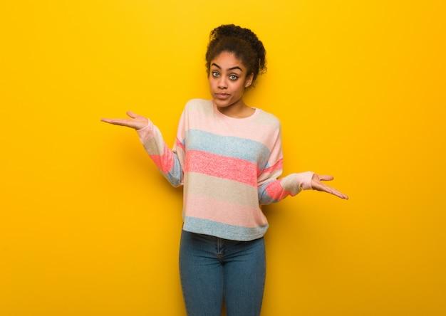 Jovem garota afro-americana negra com olhos azuis, duvidando e encolher os ombros os ombros