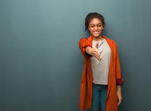 Jovem garota afro-americana negra com olhos azuis, estendendo os braços para cumprimentar alguém