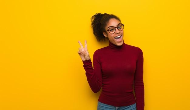 Jovem garota afro-americana negra com olhos azuis, fazendo um gesto de vitória