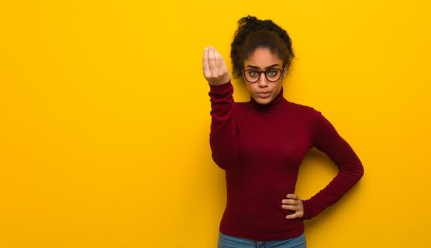 Jovem garota afro-americana negra com olhos azuis, fazendo um gesto típico italiano