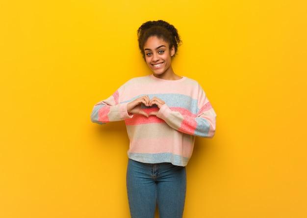 Jovem garota afro-americana negra com olhos azuis, fazendo uma forma de coração com as mãos