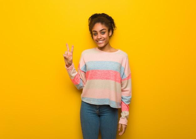 Jovem garota afro-americana negra com olhos azuis, mostrando o número dois