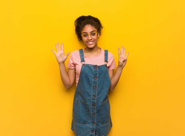 Jovem garota afro-americana negra com olhos azuis, mostrando o número nove